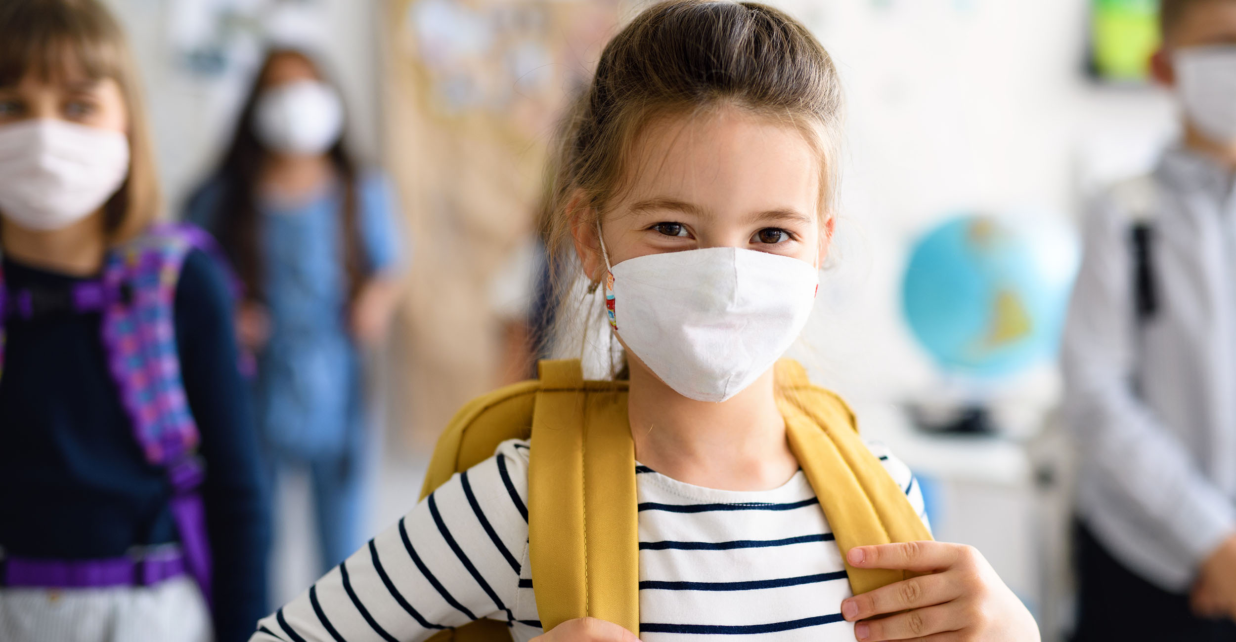 Photo of young girl wearing a protective mask in school.