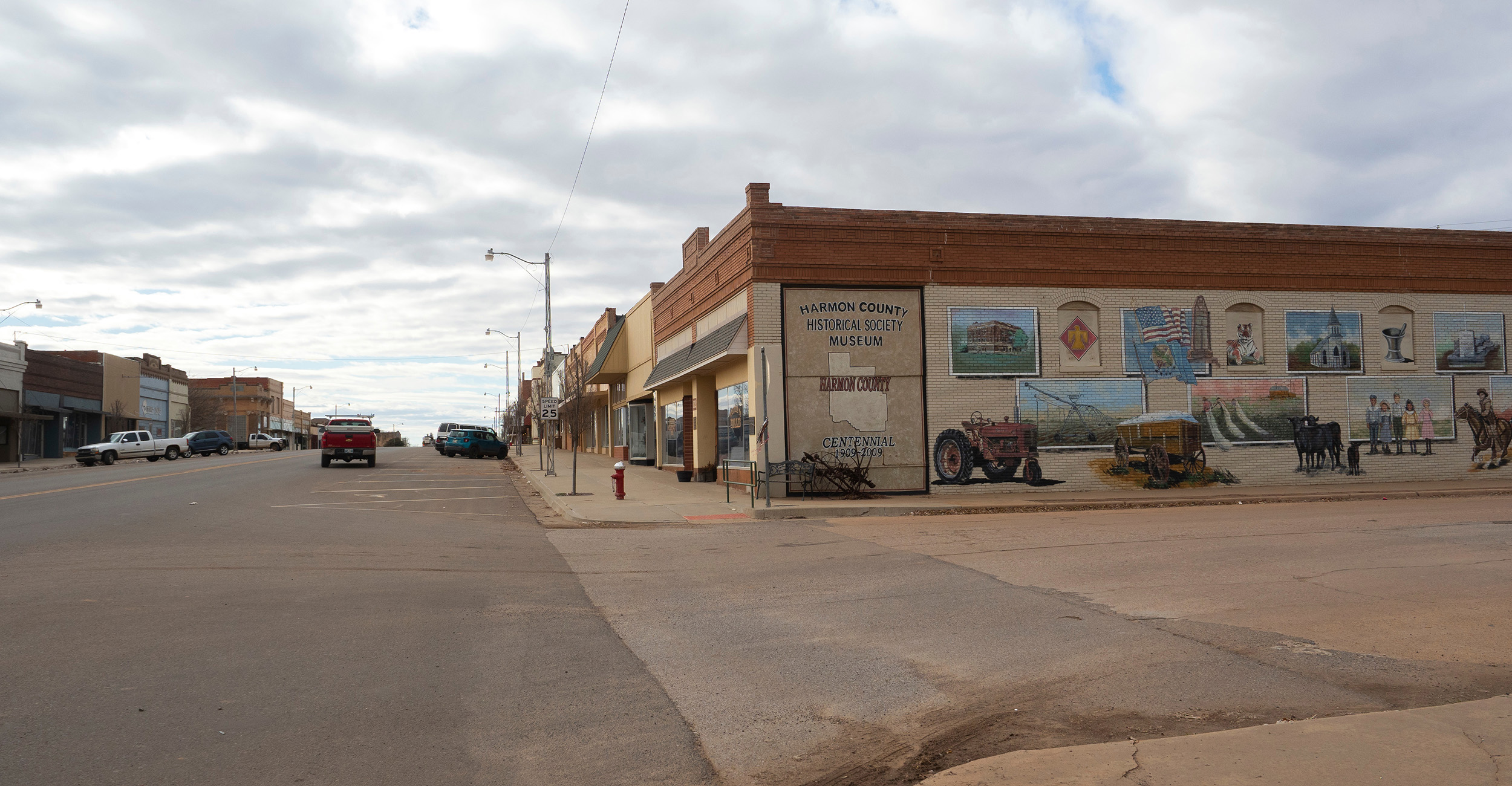 Photo of a rural town's main street with agricultural-inspired wall art.