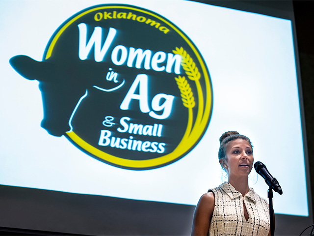 A woman talking behind the podium at the Oklahoma Women in Ag & Small Business Conference.