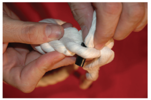 A hand with three strands of rope placing the first rope tail over unraveld strands to create a braid.