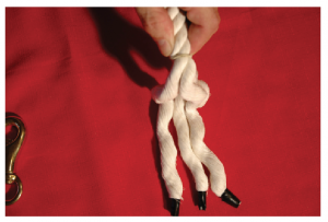 A hand holding three strands of rope after unraveling the ends of the rope.