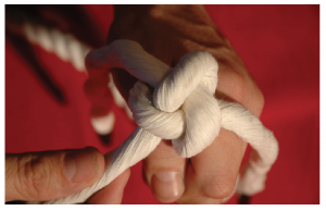 A hand with three strands of rope formed into a knot.