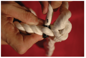 A hand holding three strands of rope and pulling the first tail through the unraveled strand.