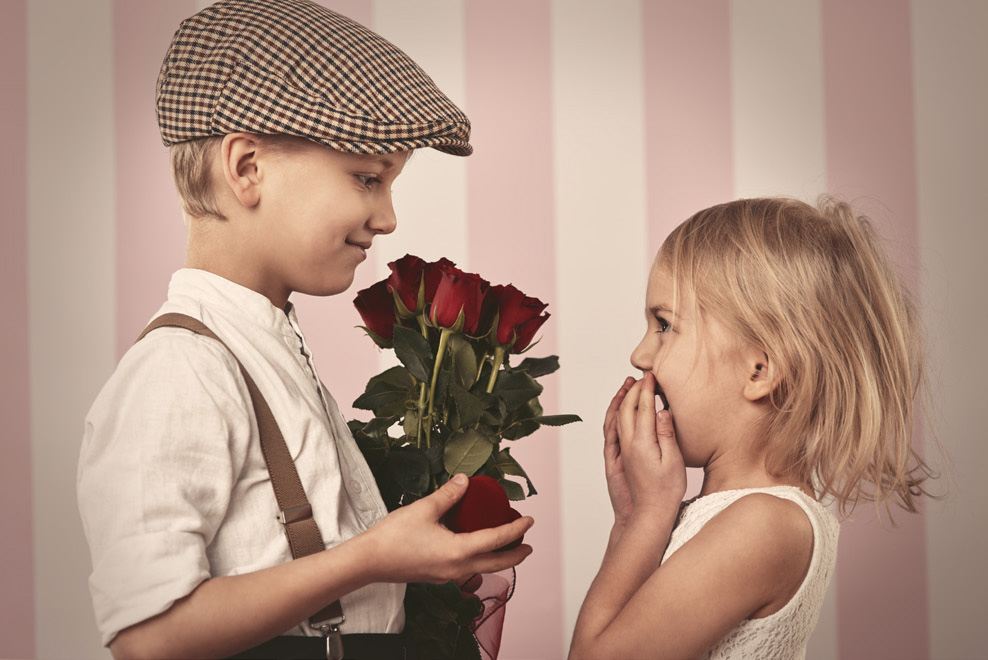 Little boy giving red roses to a little girl.