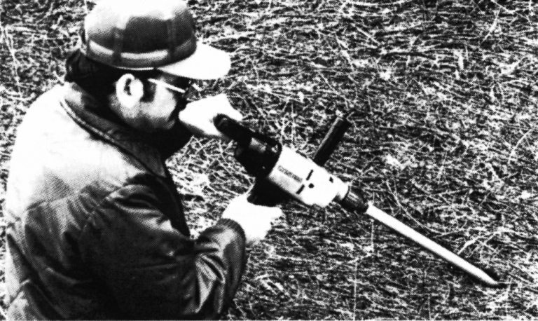 Man holding a forage probe mounted on an electric drill.
