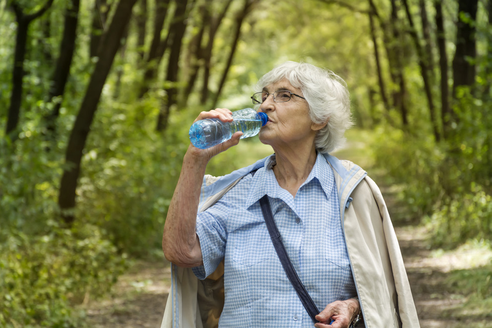 An older woman drinking a bottle of water in the woods.