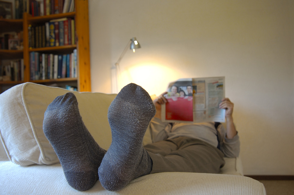 Woman lays on the couch with her feet up and reads the newspaper.
