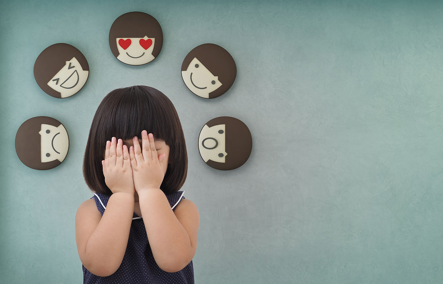A young girl holding her hands over her face with different emotions surrounding her head.