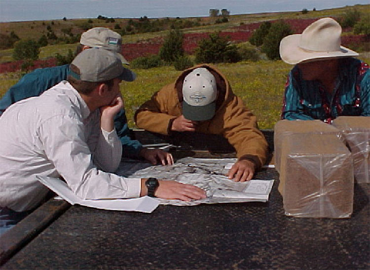 Four individuals reviewing a map.