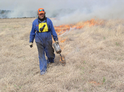 A man wearing protective uniform setting fire to grass.