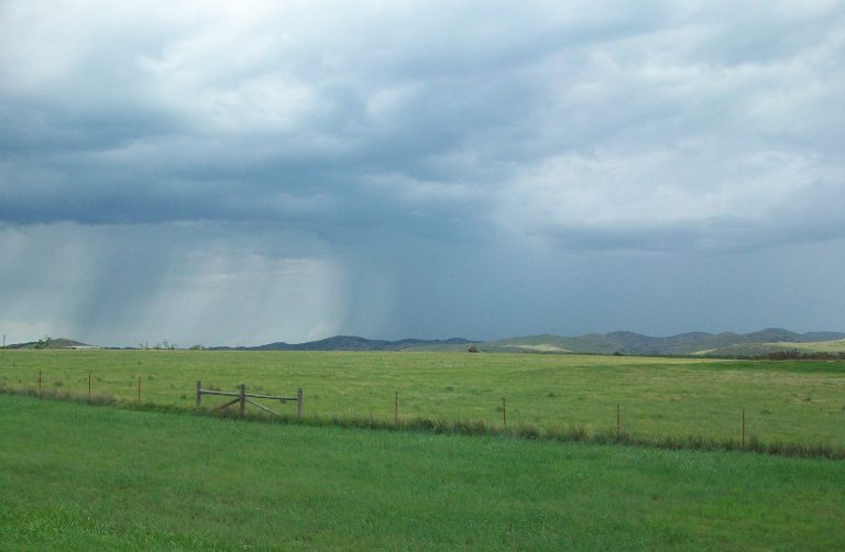 A rain storm over some fields.