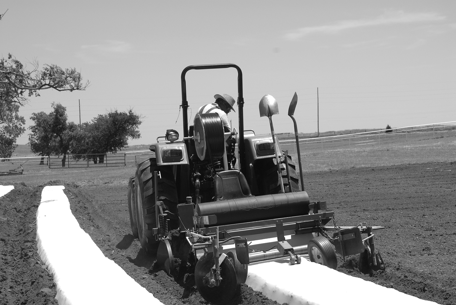 Tractor-mounted bed shaping and simultaneous application of drip tape and plastic film to rows.