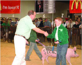 A boy shaking a man's hand in the show ring.