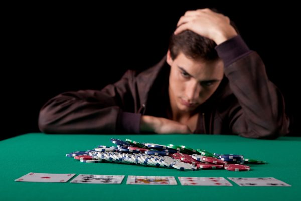 Man looking at poker chips and playing cards.