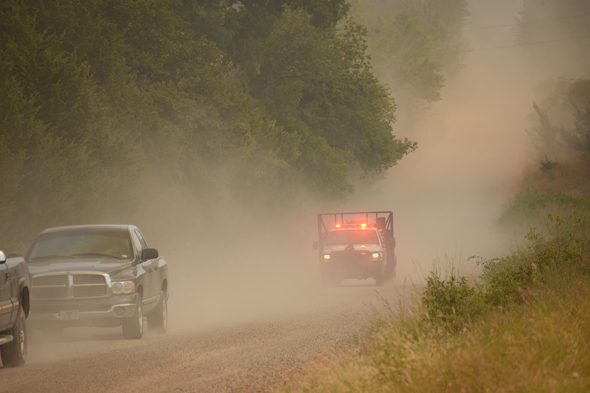 Cars are driving fast down a dirt road to evacuate.