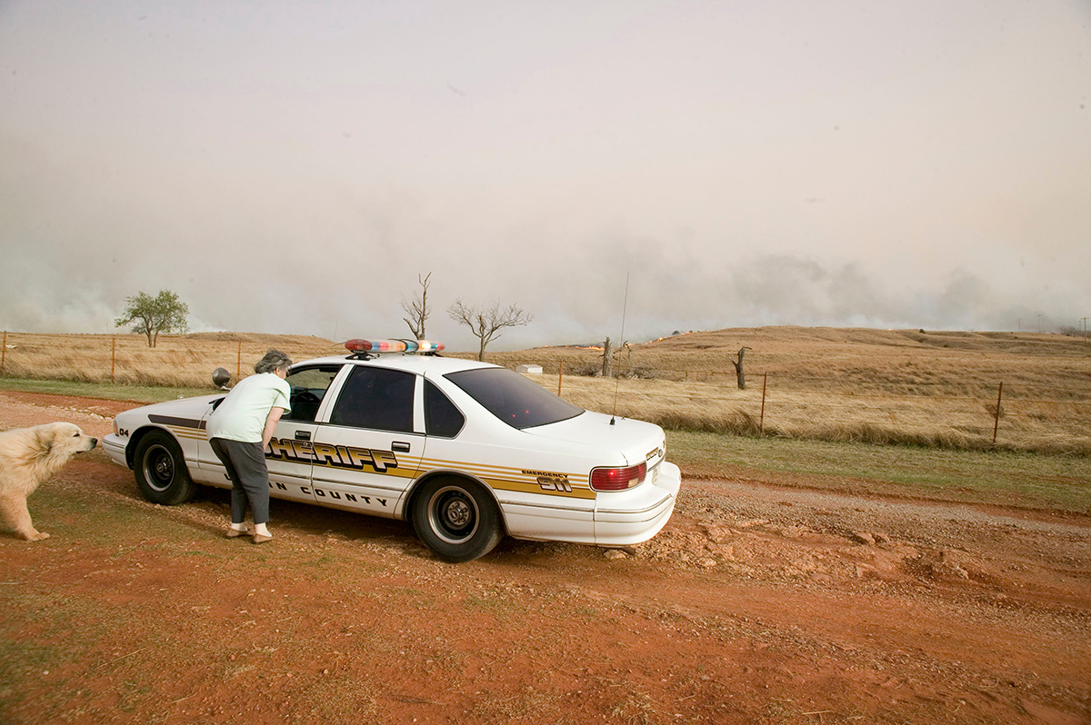 Sheriff car is stopped on a dirt road talking to a neightbor.
