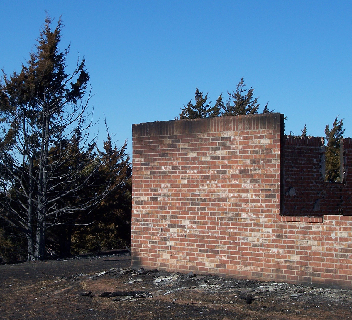 A red brick wall is the only thing left standing from a fire.