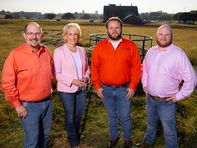 The SunUp TV team standing in a field in front of a barn.