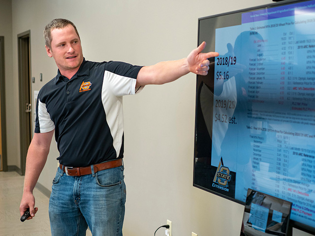 A man using a large screen to give a presentation.