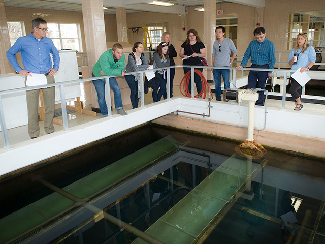 A group of people observing an indoor water tank.
