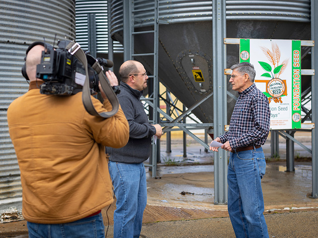 The SunUp TV members filming a segment in front of grain bins.